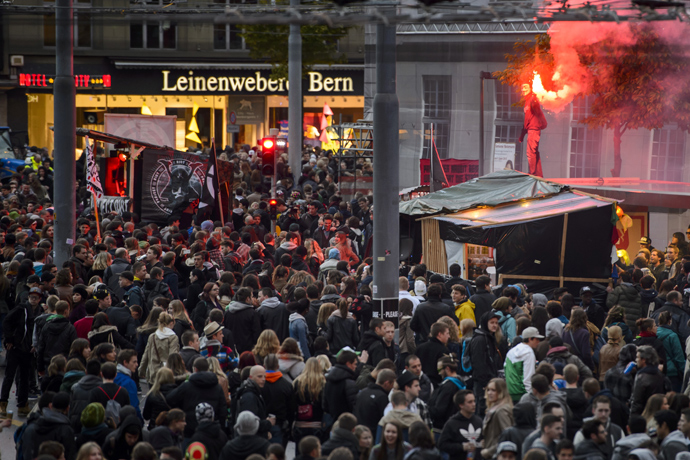 A man lights a flare on May 25, 2013 in the center of Bern (AFP Photo / Fabrice Coffrini)