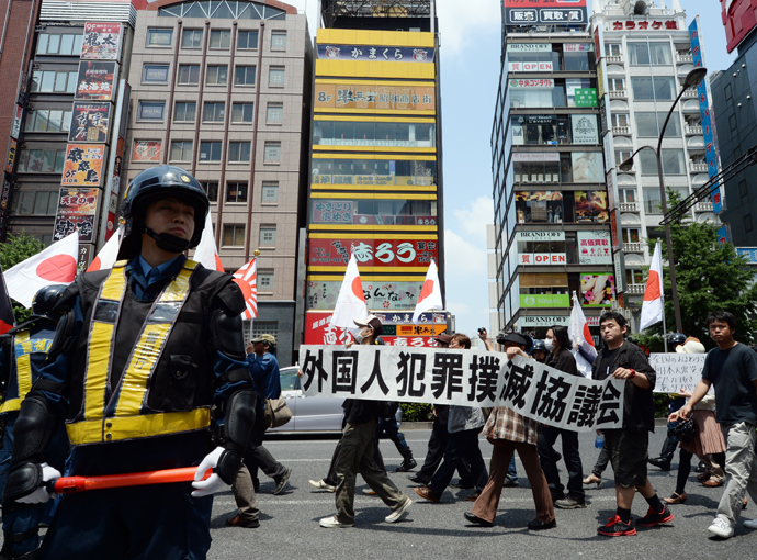 Riot police officers stand guard as demonstrators carrying Japanese flags march in a protest against crimes caused by foreign residents in Japan in the Shinjuku shopping district in Tokyo on May 26, 2013. Almost 100 rightists staged the protest march (AFP Photo / Toshifumi Kitamura)
