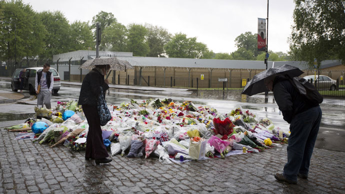 People look at floral tributes left at the scene where Drummer Lee Rigby of the 2nd Battalion was killed outside Woolwich Barracks in London on May 24, 2013.(AFP Photo / Justin Tallis)
