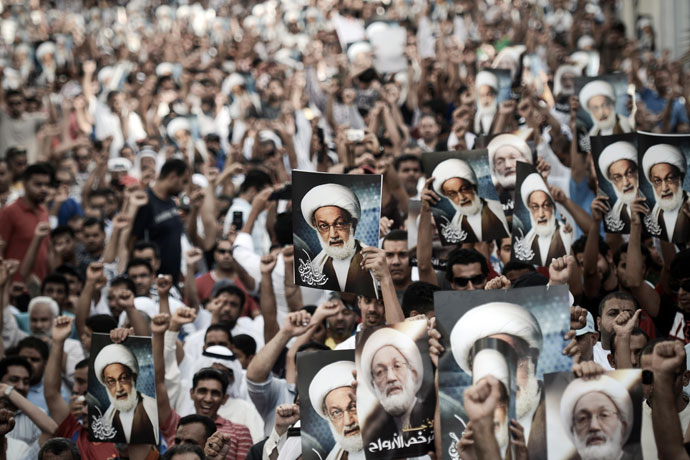 Bahraini protestors shout slogans and hold up pictures of Bahraini top senior shiite cleric, Sheikh Isa Qassim, during an anti-government rally to support Qassim in the village of Diraz, west of the capital Manama, on May 24, 2013.(AFP Photo / Mohammed Al-Shaikh)