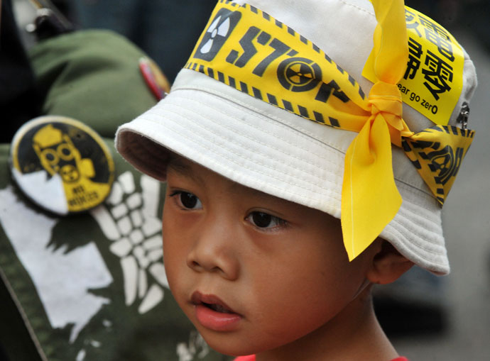 A little boy wearing hat with a yellow protest sign is seen at a demonstration against Taiwan's controversial fourth nuclear power plant at a gathering in Taipei on May 26, 2013 .(AFP Photo / Mandy Cheng)