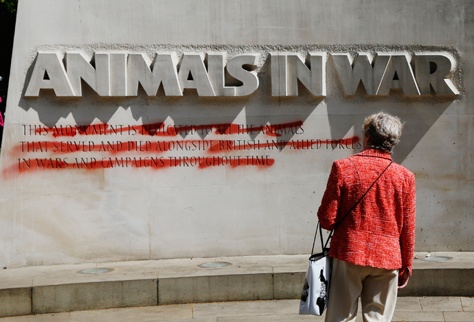 "A woman looks at the ""Animals at War"" memorial, which has been defaced with red paint, in central London May 27, 2013 (Reuters / Luke MacGregor)"