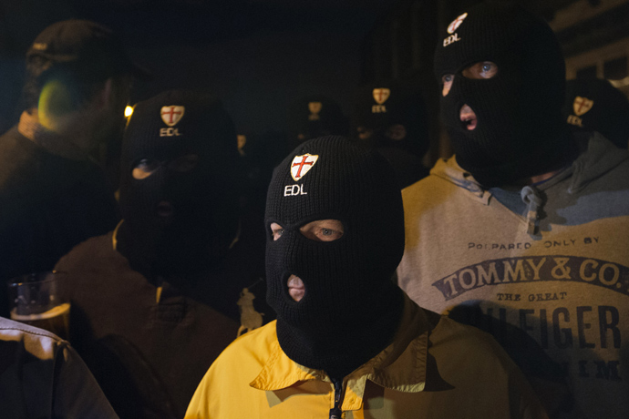 Members of the English Defence League (EDL) wear balaclavas as they gather outside a pub in Woolwich in London on May 22, 2013 after a man believed to be a serving British soldier was brutally murdered nearby in what Prime Minister David Cameron said appeared to be a terrorist attack (AFP Photo / Justin Tallis)