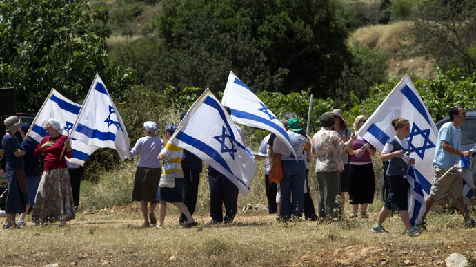 Jewish settlers from the settlements of Gush Etzion and Kiryat Arba wave Israeli flags as they gather on Route 60, mainly used by settlers, near the Palestinian village of Al-Khader in the occupied West Bank on May 24, 2013.(AFP Photo / Ahmad Gharabli)
