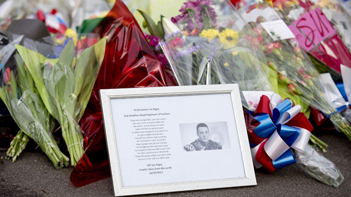 A framed photograph of Drummer Lee Rigby lies amongst floral tributes outside Woolwich Barracks in London on May 23, 2013.(AFP Photo / Justin Tallis)
