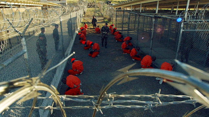 Detainees in orange jumpsuits sit in a holding area under the watchful eyes of military police during in-processing to the temporary detention facility at Camp X-Ray of Naval Base Guantanamo Bay (Reuters / Stringer)