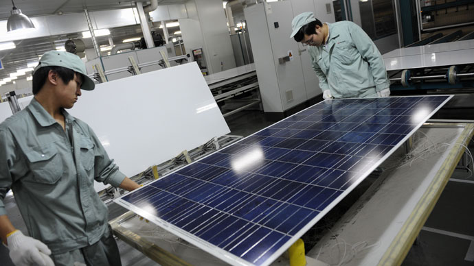 Workers assembling solar panels by hand on the factory floor of Chinese company Suntech in the eastern Chinese city of Wuxi.(AFP Photo / Peter Parks)