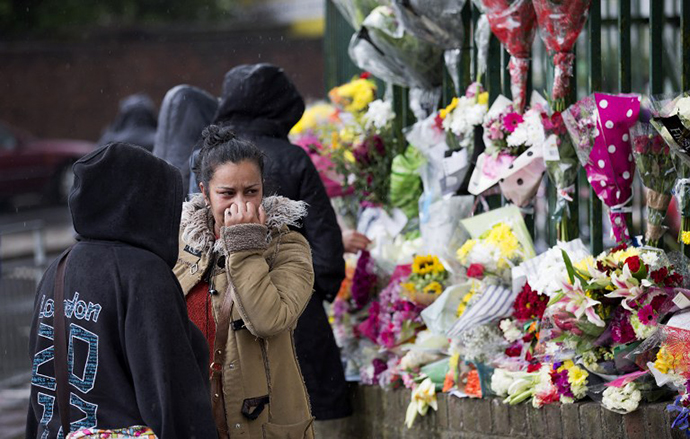A woman reacts as she looks at floral tributes left at the scene where Drummer Lee Rigby of the 2nd Battalion was killed outside Woolwich Barracks in London on May 24, 2013. (AFP Photo / Justin Tallis)