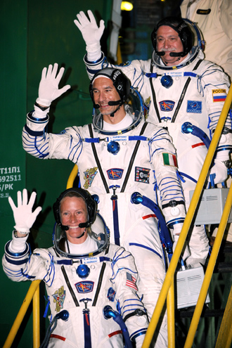 US astronaut Karen Nyberg (bottom), Russian cosmonaut Fyodor Yurchikhin (C) and European Space Agency (ESA) Italian astronaut Luca Parmitano wave as they board the Soyuz TMA-09M spacecraft at the Russian-leased Baikonur cosmodrome on May 29, 2013 (AFP Photo / Kirill Kudryavtsev)