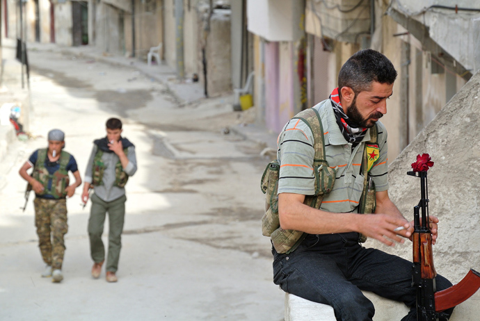 A rebel fighter of the Syrian Kurdish Popular Protection Units (YPG) has a flower in his Russian made 'AK-47' kalashnikov gun as he holds a position in the Sheikh Maqsoud neighbourhood in the Syrian city of Aleppo on May 9, 2013 (AFP Photo / Str)
