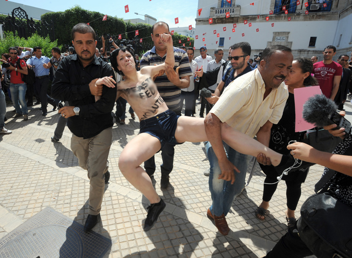 One of three topless activists from the Femen feminist group, is arrested by a plainclothed policemen as they demonstrate in front of the justice Palace in Tunis, on May 29, 2013 (AFP Photo / Fethi Belaid)