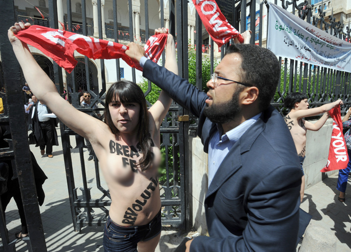 A lawyer tries to snatch a banner being held by one of three activists from the Femen feminist group, as they demonstrate in front of the justice Palace in Tunis, on May 29, 2013, before being arrested (AFP Photo / Fethi Belaid)