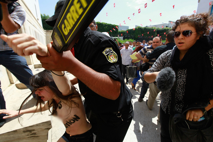 Police officers detain an activist from the women's rights group FEMEN during a protest against the arrest of their Tunisian member named Amina, in front of Tunisia's Ministry of Justice in Tunis, May 29, 2013 (Reuters / Anis Mili)