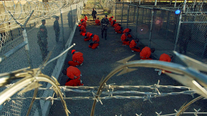 Detainees in orange jumpsuits sit in a holding area under the watchful eyes of military police during in-processing to the temporary detention facility at Camp X-Ray of Naval Base Guantanamo Bay.(Reuters / Stringer)