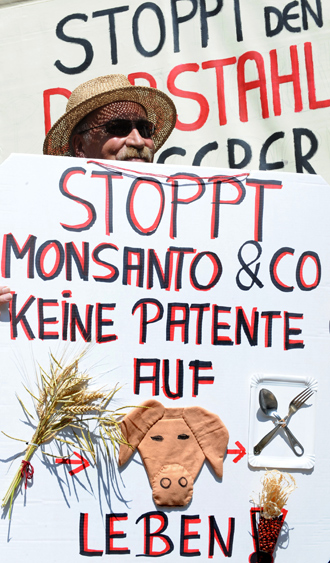 "A man protests with placards reading ""No patents on on life, stop Monsanto"" during a demonstration against food patents in front of the patent office in Munich, southern Germany (AFP Photo)"