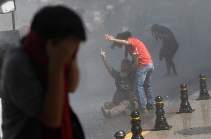 A demonstrator reacts as riot police use a water cannon and tear gas to disperse the crowd during a protest against the destruction of trees in a park brought about by a pedestrian project, in Taksim Square in central Istanbul May 31, 2013 (Reuters / Murad Sezer)