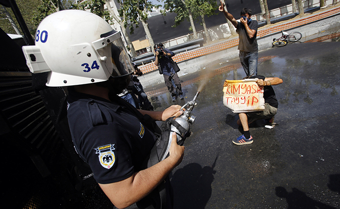 "A Turkish riot policeman uses tear gas as a demonstrator holds a banner which reads that, ""Chemical Tayyip"", referring to Prime Minister Tayyip Erdogan, during a protest against the destruction of trees in a park brought about by a pedestrian project, in Taksim Square in central Istanbul May 31, 2013. (Reuters / Murad Sezer)"