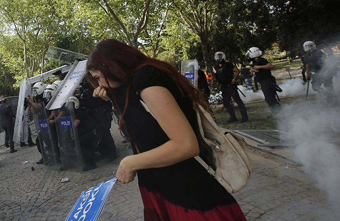 A demonstrator covers her face as riot police use tear gas to disperse the crowd during a protest against the destruction of trees in a park brought about by a pedestrian project, in Taksim Square in central Istanbul May 31, 2013. (Reuters / Murad Sezer)