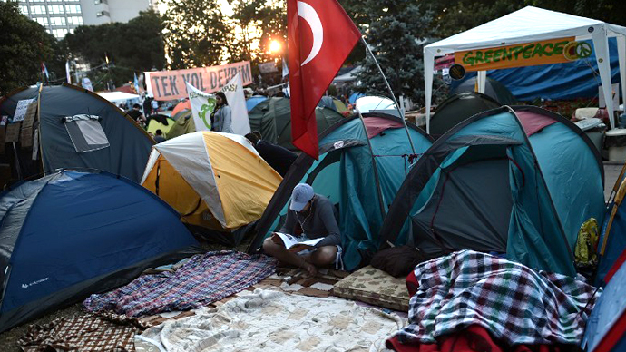 A demonstrator reads a magazine, amongst tents in Gazi park next to Taksim square in Istanbul early on June 8, 2013. (AFP Photo / Aris Messinis)