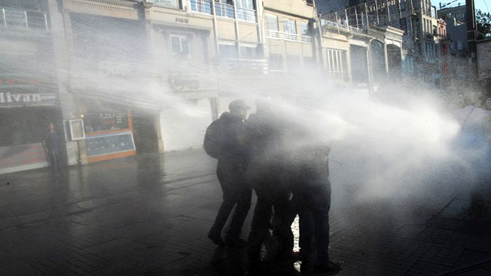 Protesters take cover from a water cannon during clashes with police on Istiklal Avenue in Istanbul on July 8, 2013. (AFP Photo / Bulent Kilic)
