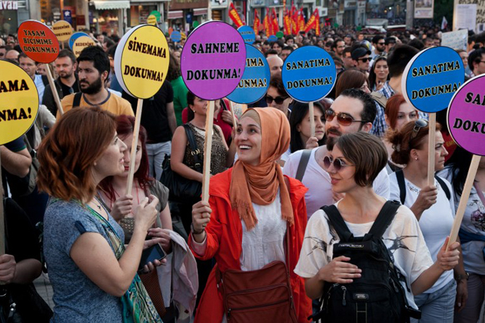 "Demonstrators hold placards reading ""Dont touch my cinema (L), dont touch my stag e(2nd-L), dont touch my art (R), dont touch my life style (back-R) as they stand during a protest at Taksim square in Istanbul on June 7, 2013. (AFP Photo / Gurcan Ozturk)"