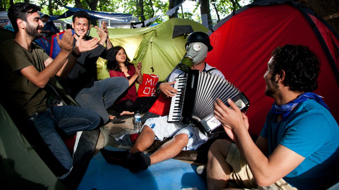 A demonstrator wearing a gas mask plays the accordeon as he sits with others near a tent at a makeshipt camp on Taksim square in Istanbul on June 7, 2013. (AFP Photo / Gurcan Ozturk)