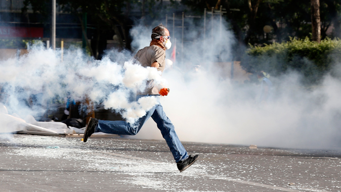 A demonstrator runs as he throws a tear gas canister back at riot police during a protest against Turkey's Prime Minister Tayyip Erdogan and his ruling AK Party in central Ankara June 2, 2013 (Reuters / Umit Bektas)