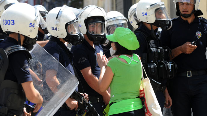 A women asks police to stop as Turkish protestors and riot policemen clash in Taksim Square in Istanbul on June 1, 2013. (AFP Photo / Bulent Kilic)