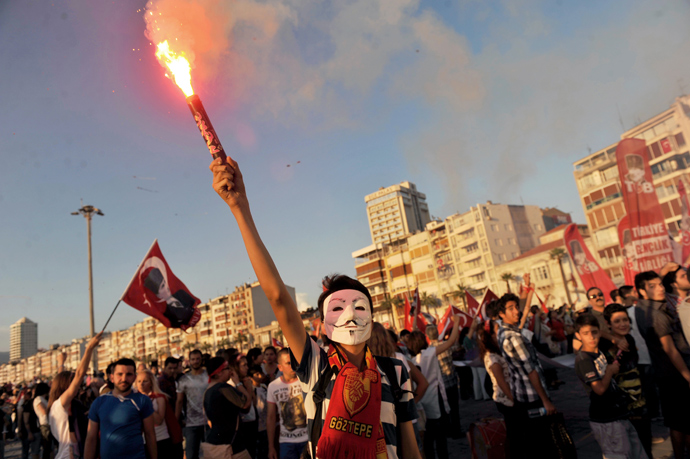 A Turkish demostrator burns flares with a Guy Fawkes mask on June 8, 2013 during a demonstration on Gundogdu square in Izmir (AFP Photo / Ozan Kose)