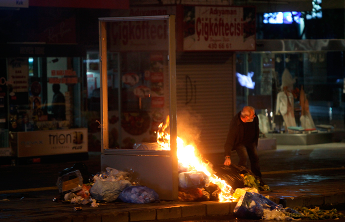 A protester places some trash into a fire in central Ankara, June 9, 2013 (Reuters / Dado Ruvic)