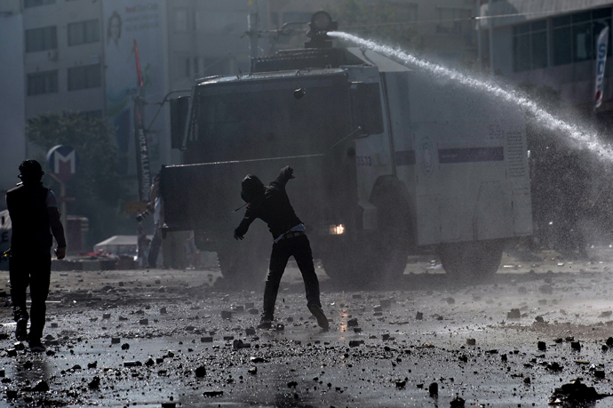 A protester throws a stone at a water canon during clashes with riot police in istanbul's Taksim square on June 11, 2013 (AFP Photo/ Aris Messinis)