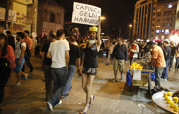 "A gay rights activist holds a sign as he protests near Taksim Square in Istanbul June 7, 2013. The sign reads, ""The looter is coming, ladies"" (Reuters / Stoyan Nenov)"
