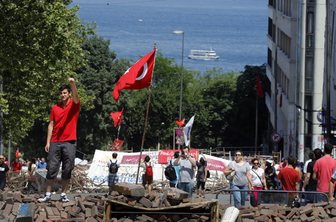 A man poses for a picture on top of a barricade set by anti-government protesters near Istanbul's Taksim square June 8, 2013. (Reuters / Yannis Behrakis)