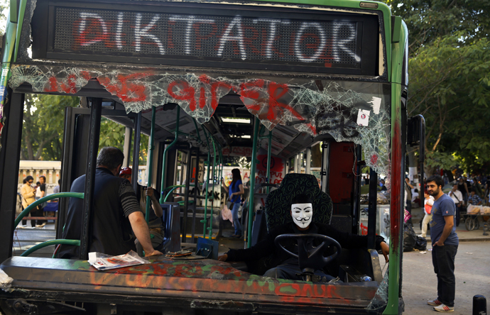 A protester sits inside a damaged bus used by anti-government protesters as a barricade in Istanbul's Taksim square June 10, 2013. (Reuters / Yannis Behrakis)