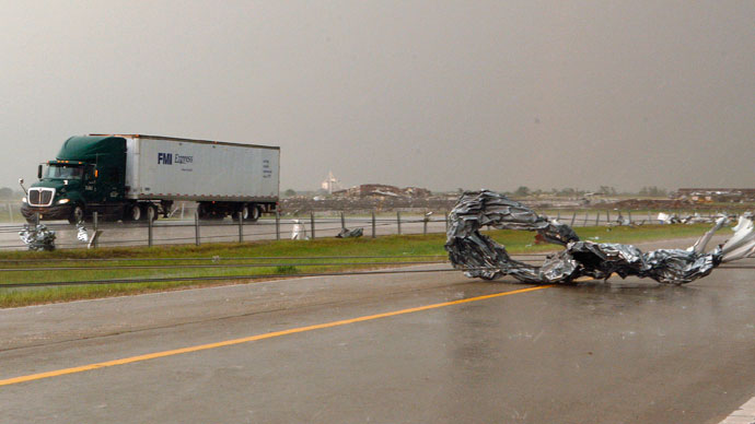 Tornado debris and downed power lines are seen at Interstate-40 Westbound as traffic slowly passes in the opposite direction of Interstate-40, just east of El Reno, Oklahoma May 31, 2013.(Reuters / Bill Waugh)