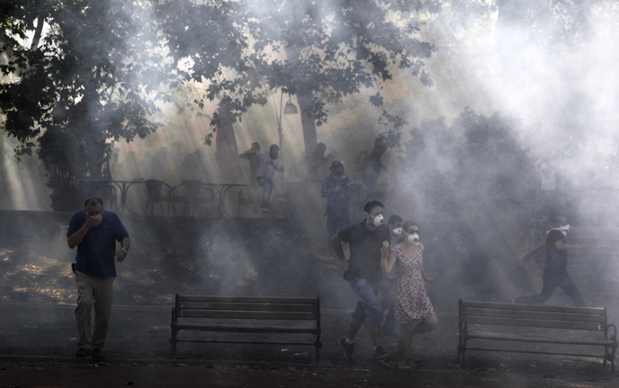 Protestors run away from tear gas at the Taksim Gezi park in Istanbul after clashes with riot police, on June 1, 2013, during a demonstration against the demolition of the park (AFP Photo / Gurcan Ozturk)
