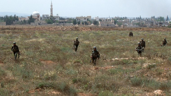 A handout picture released by the Syrian Arab News Agency (SANA) on May 30, 2013, shows Syrian army soldiers walking nearby facilities of Dabaa military airfield during an operation that led to the control of the airport, north of the Syrian city of Qusayr. (AFP Photo / SANA)