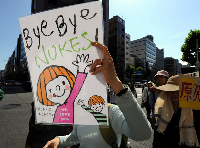 A protestor holds a banner during a protest march against nuclear power plants, following the March 2011 Fukushima meltdown-disasters, in Tokyo on June 2, 2013. (AFP Photo / Toshifumi Kitamura)