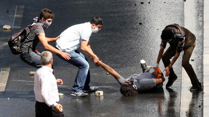 An injured demonstrator is helped during clashes between riot police and demonstrators in Ankara on June 1, 2013. (AFP Photo / Adem Altan)