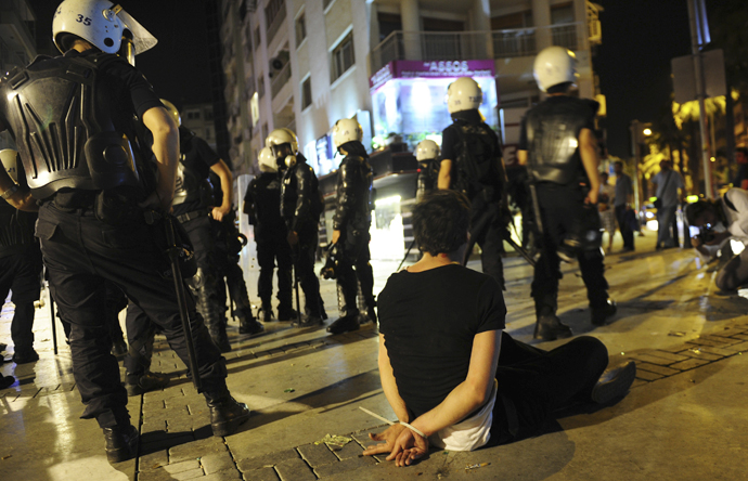 A demonstrator sits on the ground after he was detained by riot police during an anti-government protest in Izmir, western Turkey, June 2, 2013. (Reuters)
