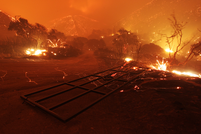 Wind-blown embers fly around fallen gates immediately after the main fire front sweeps over in a fast run toward Lake Hughes on June 1, 2013 south of Lake Hughes, California (AFP Photo / David McNew)