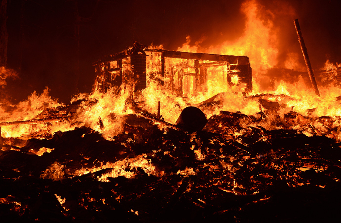Fire engulfs a house as firefighters battle the Powerhouse wildfire at the Angeles National Forest, with the fire now having destroyed several homes near the Lake Hughes area in California June 1, 2013 (Reuters / Gene Blevins)