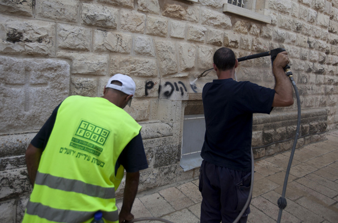 "A Jerusalem municipality worker cleans anti-Christian graffiti reading in Hebrew, ""Christians monkeys"" that was daubed on the Church of the Dormition, one of Jerusalem's leading pilgrimage sites, on May 31, 2013 (AFP Photo / Ahmad Gharabli)"
