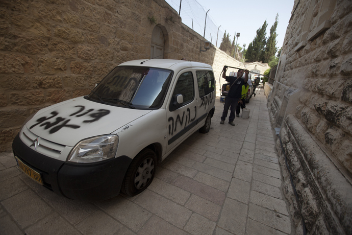 Jerusalem municipality workers clean anti-Christian graffiti that was daubed on the Church of the Dormition, one of Jerusalem's leading pilgrimage sites, early on May 31, 2013 (AFP Photo / Ahmad Gharabli)