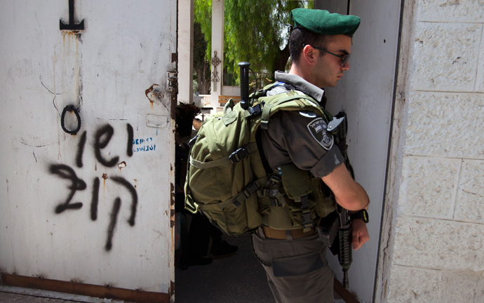 "An Israeli border guard stands next to anti-Christian graffiti reading in Hebrew, ""Jesus is monkey"" that was daubed on the Church of the Dormition, one of Jerusalem's leading pilgrimage sites, early on May 31, 2013 (AFP Photo / Ahmad Gharabli)"