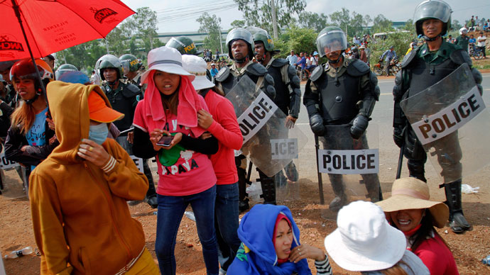 Garment workers stand near police officers during a protest in front of a factory owned by Sabrina (Cambodia) Garment Manufacturing in Kampong Speu province, west of the capital Phnom Penh June 3, 2013.(Reuters / Samrang Pring)