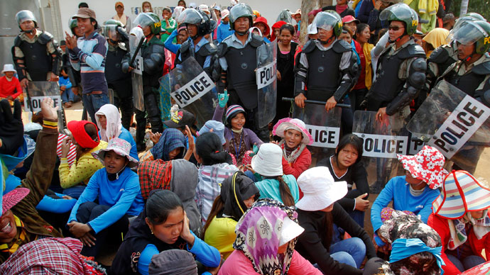 Garment workers sit beside police officers during a protest in front of a factory owned by Sabrina (Cambodia) Garment Manufacturing in Kampong Speu province, west of the capital Phnom Penh June 3, 2013.(Reuters / Samrang Pring)