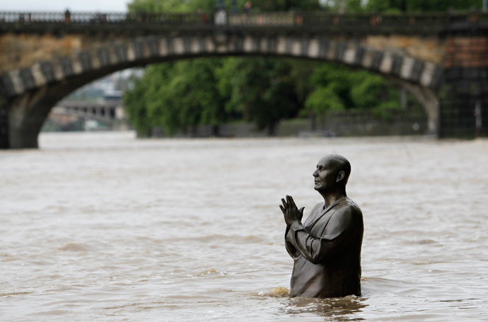 The statue of world harmony leader Sri Chinmoy is partially submerged in water from the rising Vltava river in Prague June 2, 2013 (Reuters / David W Cerny)