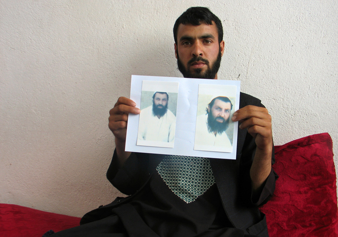 Shahedullah, 24, holds pictures of his brother Mohammad Qasim, whose body according to Shahedullah was found close to the COP Nerkh military base, in Wardak province (Reuters / Stringer)