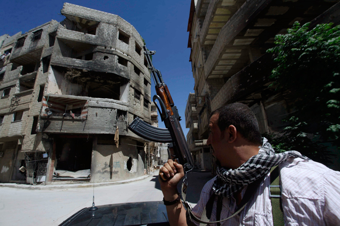 A Shi'ite fighter holds his weapon while patrolling a road at Sayeda Zainab area in Damascus (Reuters / Alaa Al-Marjani)